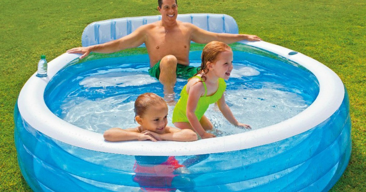 dad sitting in blue inflatable pool with kids