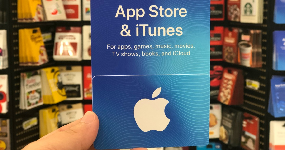 someone holding an Apple itunes gift card at a store