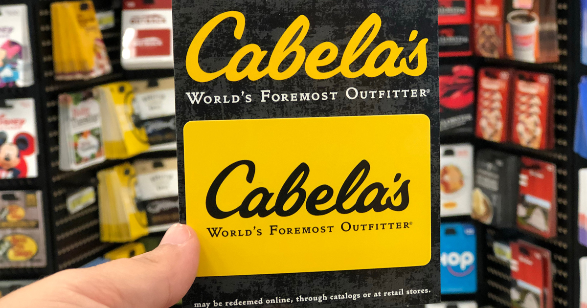 hand holding a cabelas gift card in front of a store gift card display