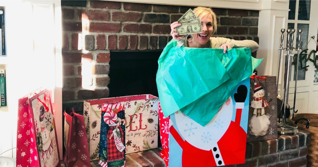 woman popping out of gift bag holding cash