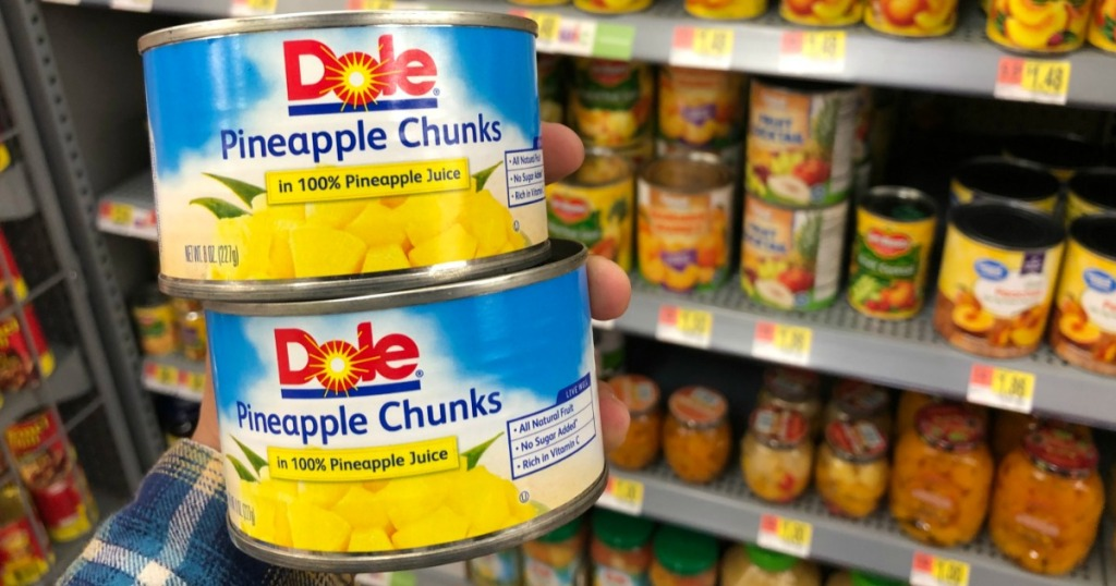 hand holding cans of dole pineapple chunks in store