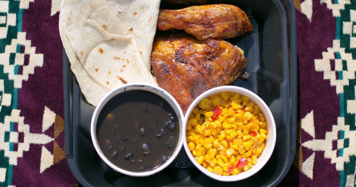 takeout container with two pieces of chicken, beans, rice, and tortillas