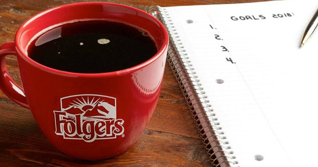 Folgers Medium Roast Coffee in a coffee mug with folgers logo on table near notebook