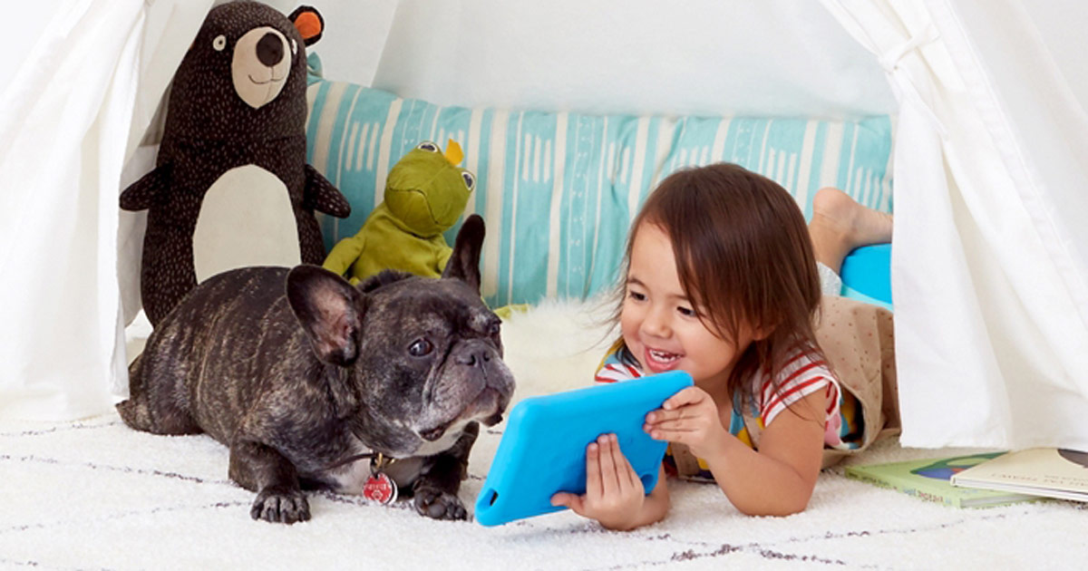little girl showing her bulldog her amazon fire tablet