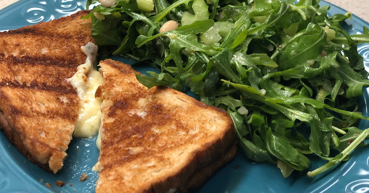 grilled cheese on plate with a bed of greens