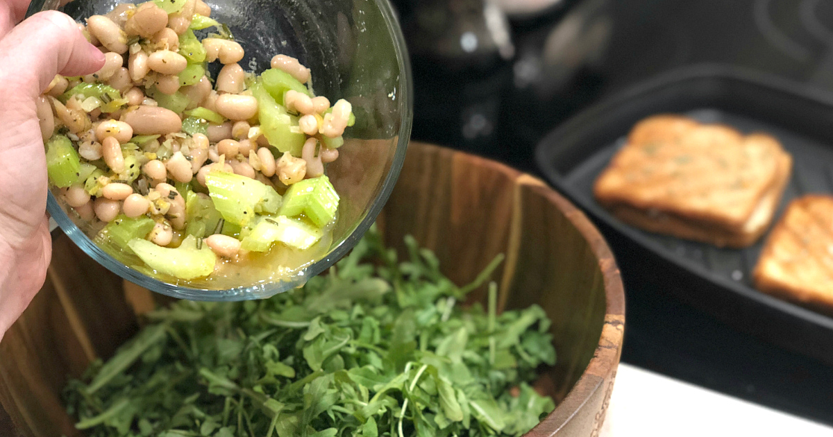 pouring beans into salad greens