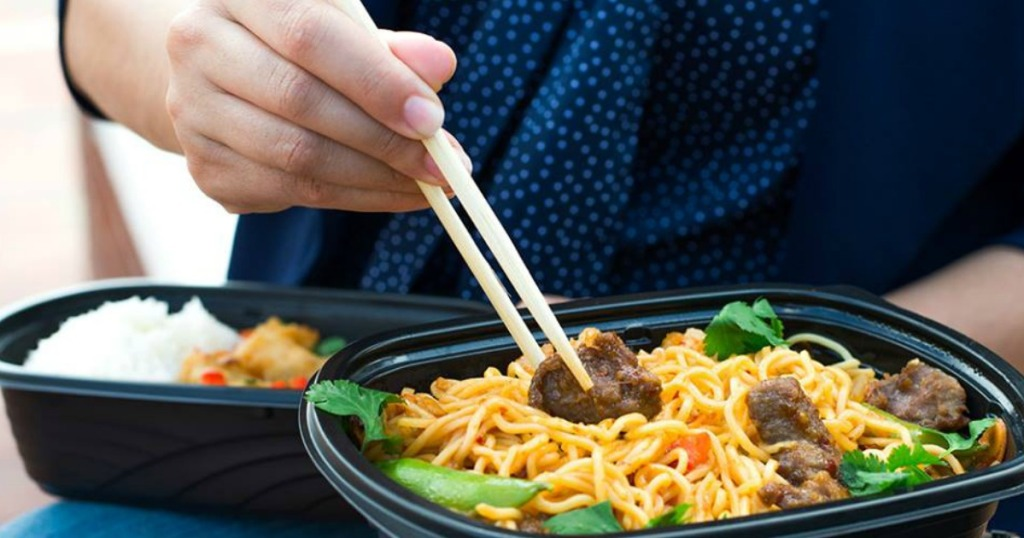 hands using chop sticks eating noodle dish