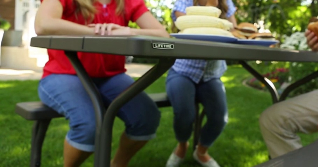 family sitting outside on picnic table