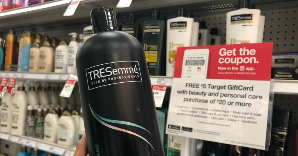 hand holding tresemme shampoo in front of gift card sign