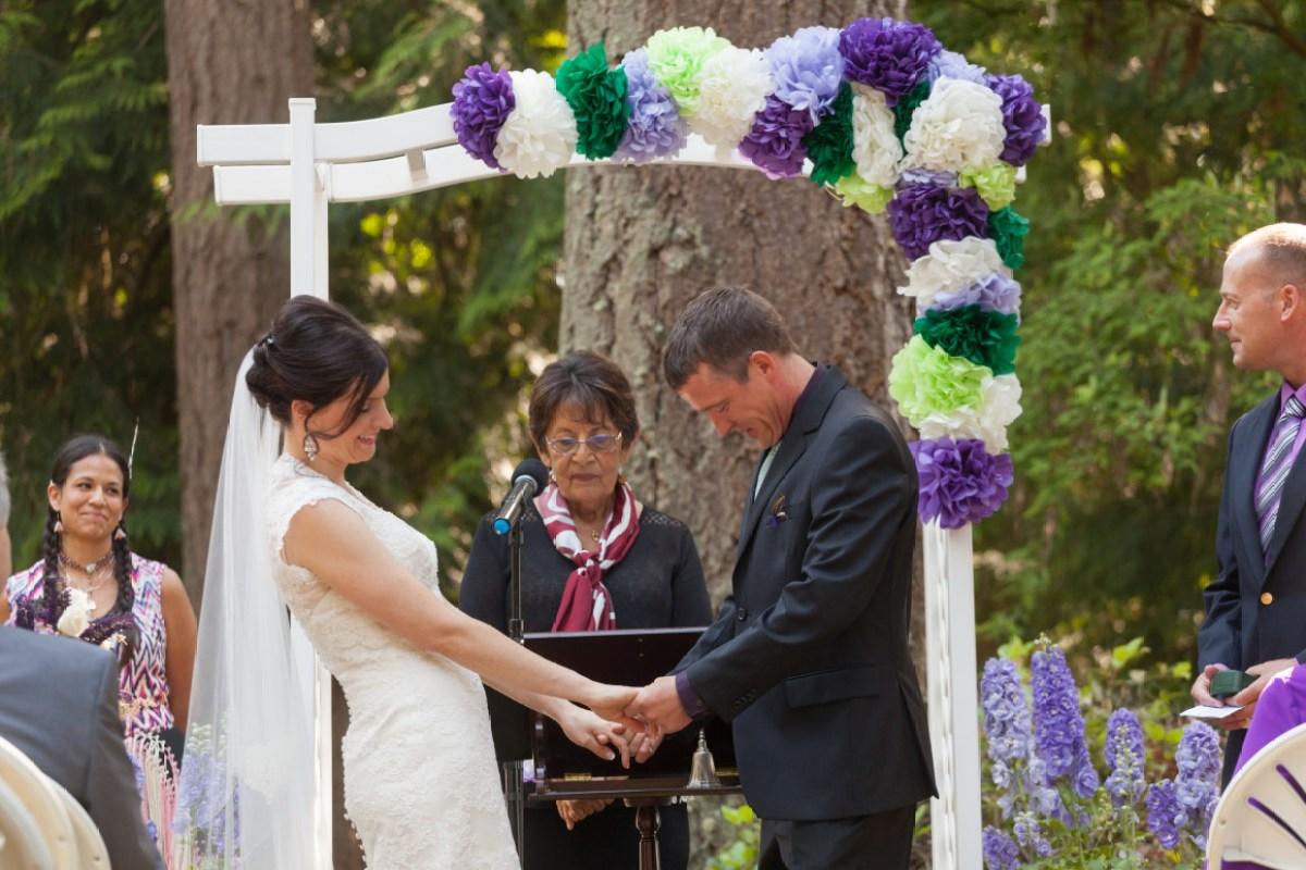 bride and groom holding hands at wedding ceremony - dollar tree wedding