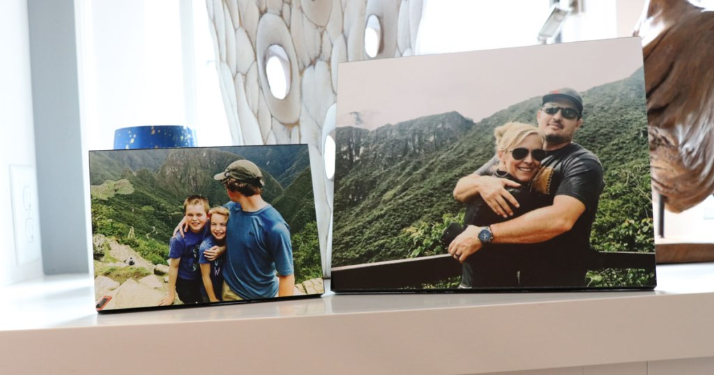 two wooden photo prints on white counter of kids and couple in the mountains