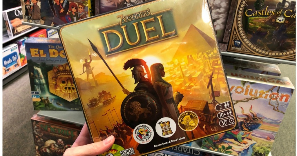 hand holding up 7 wonders duel game in store