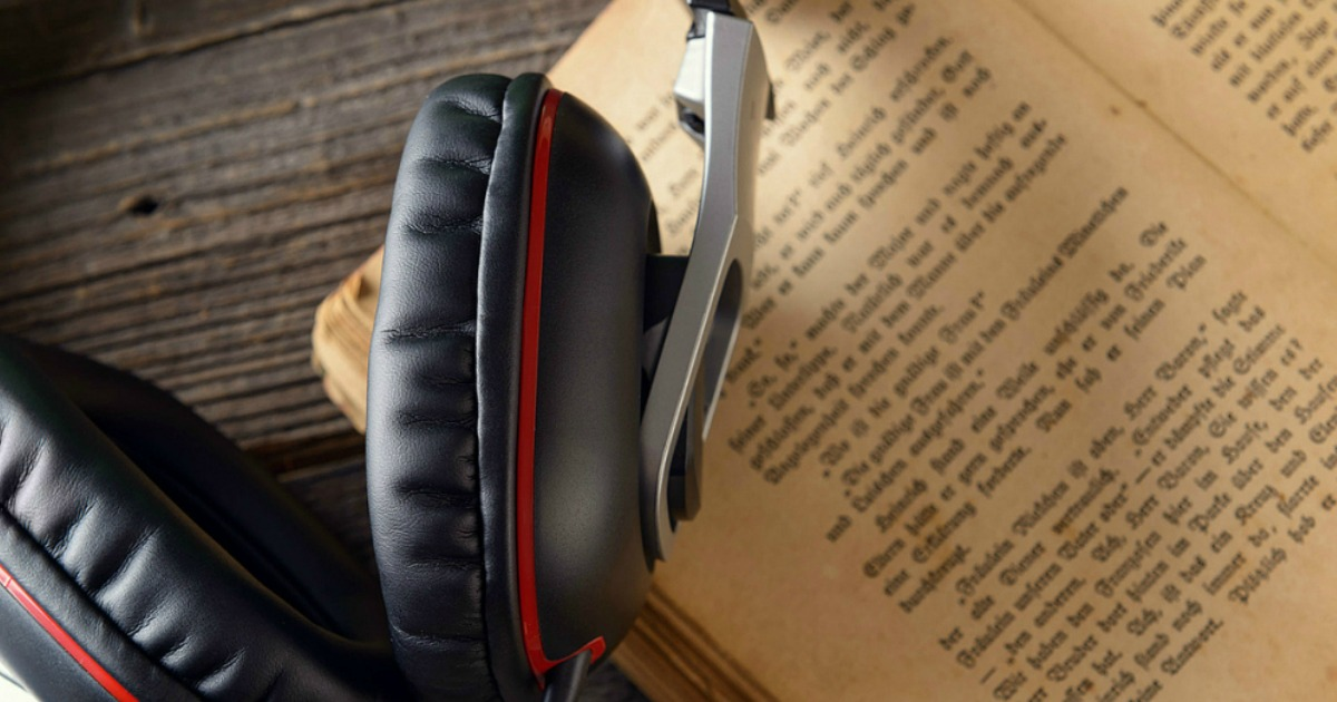 pair of headphones laying atop an old book