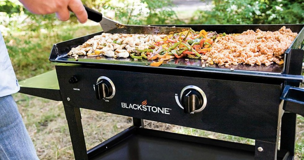 blackstone grill with meat and veggies on it