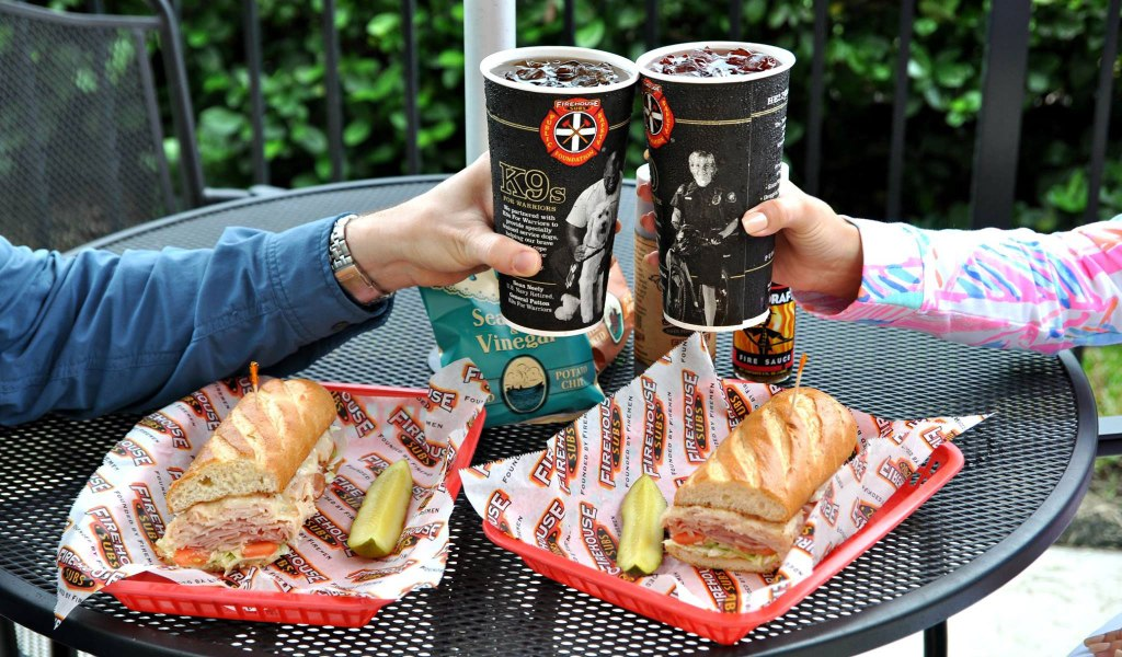 doing a cheers with soda over two Firehouse subs in baskets