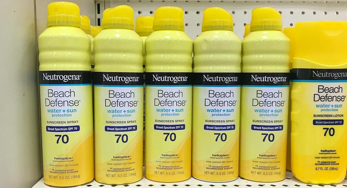 Row of yellow Neutrogena beach defense sunscreen bottles on store shelves