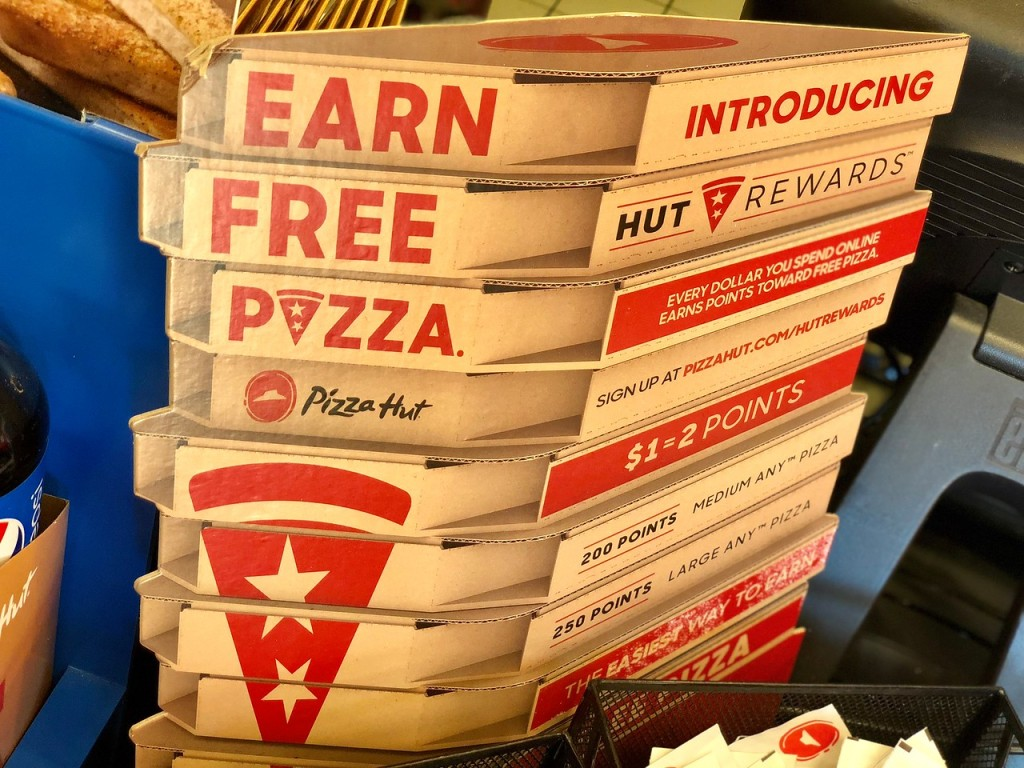 Stack of pizza hut boxes with wording on the side of boxes that says earn free pizza
