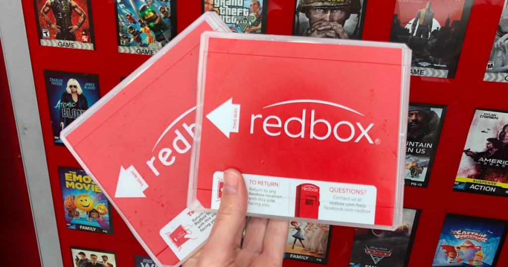 person holding two redbox dvds