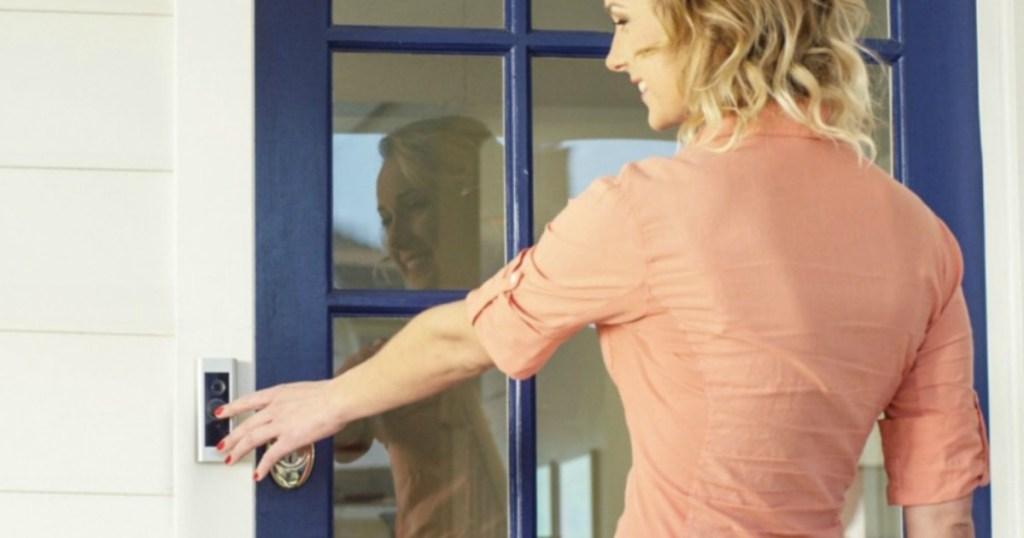 woman pressing Ring Doorbell Pro at front door of house