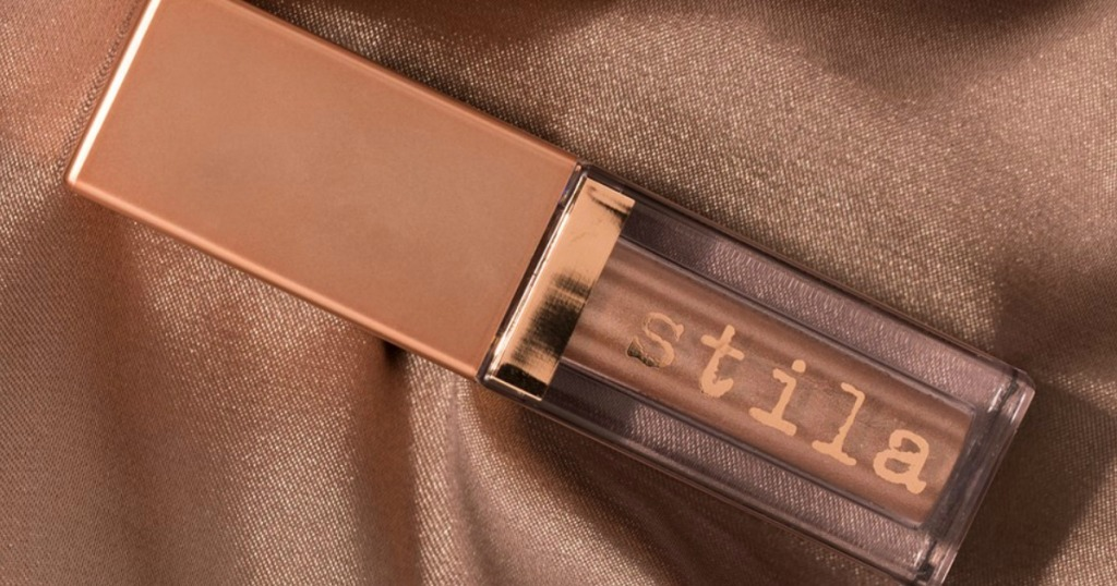 bottle of Stila Shimmer & Glow on a brown shiny fabric background