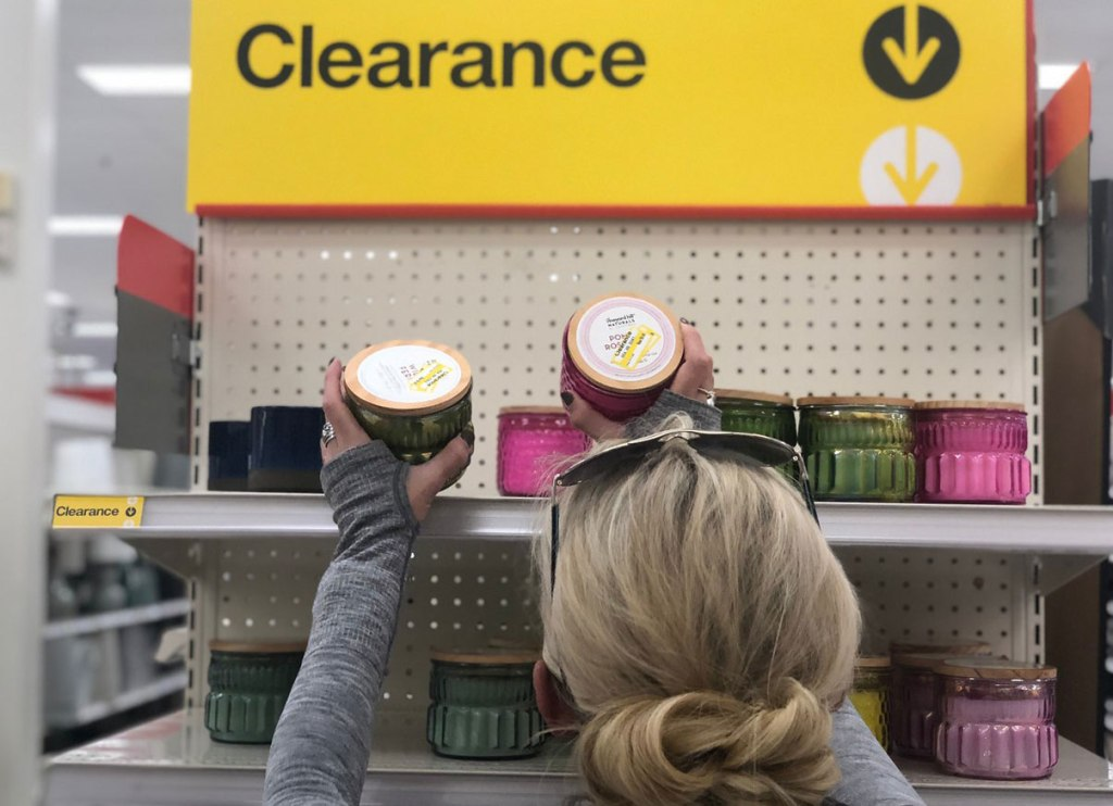 woman picking up clearance candles at Target