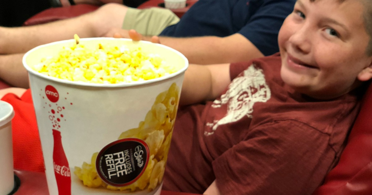 Young boy with popcorn smiling at the camera