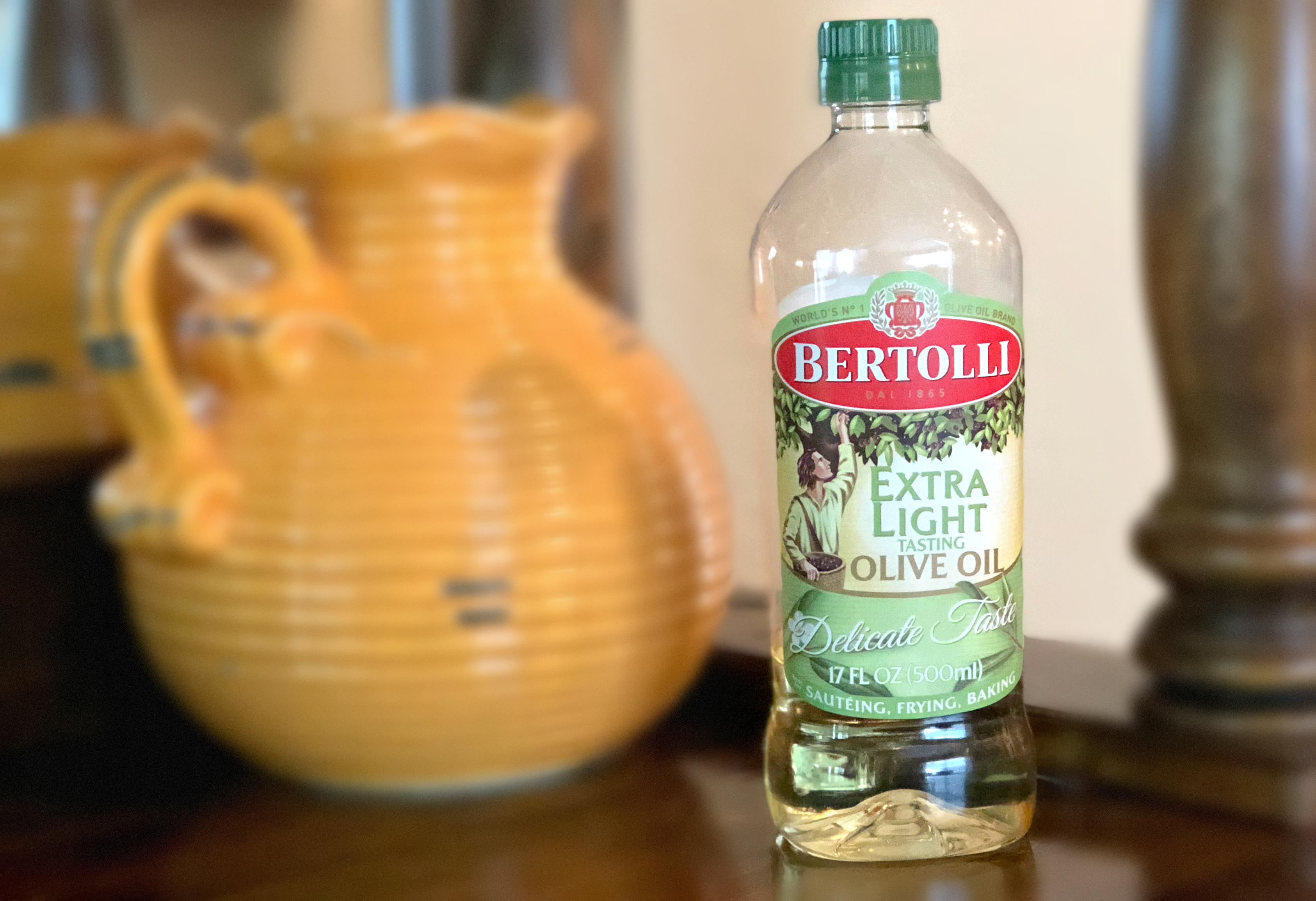 Bertolli Extra Light Tasting olive oil next to an earthenware jug
