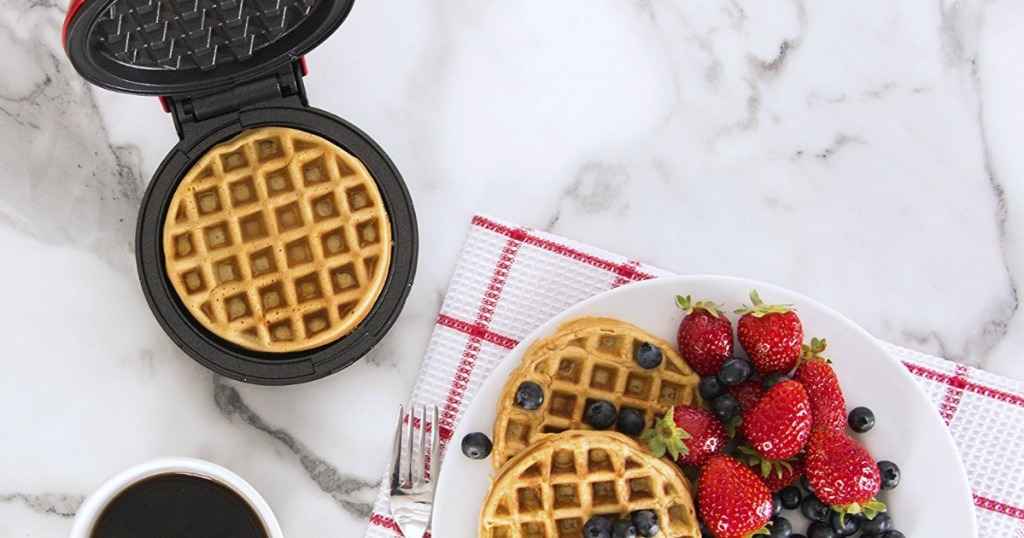 mini waffle maker next to a plate of waffles and fruit