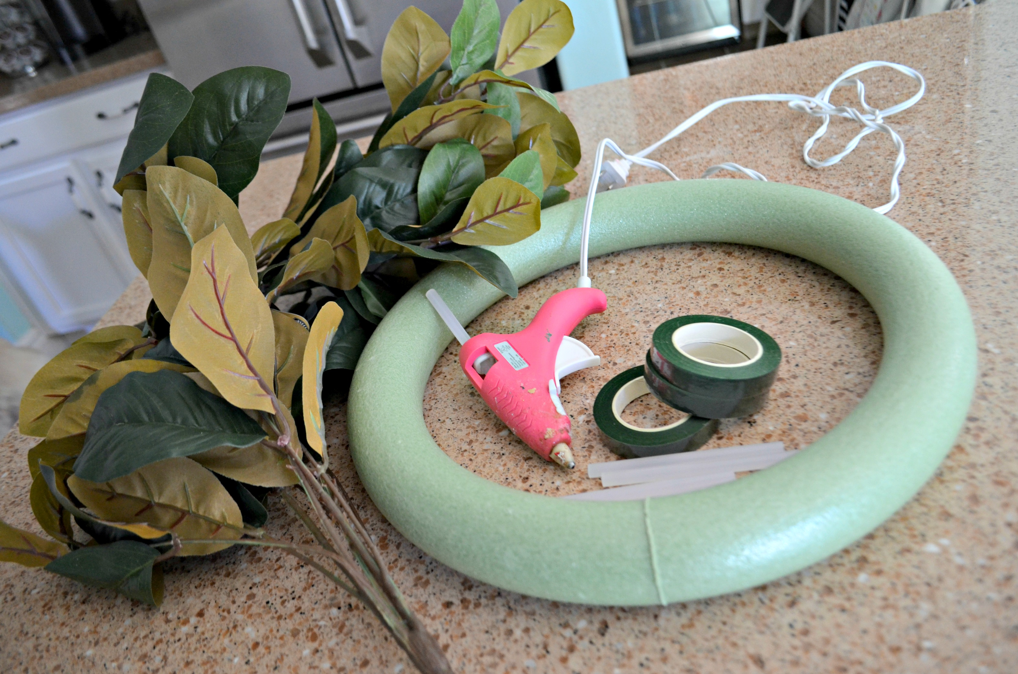 Items to make my DIY magnolia wreath: leaves, foam form, hot glue, floral tape.