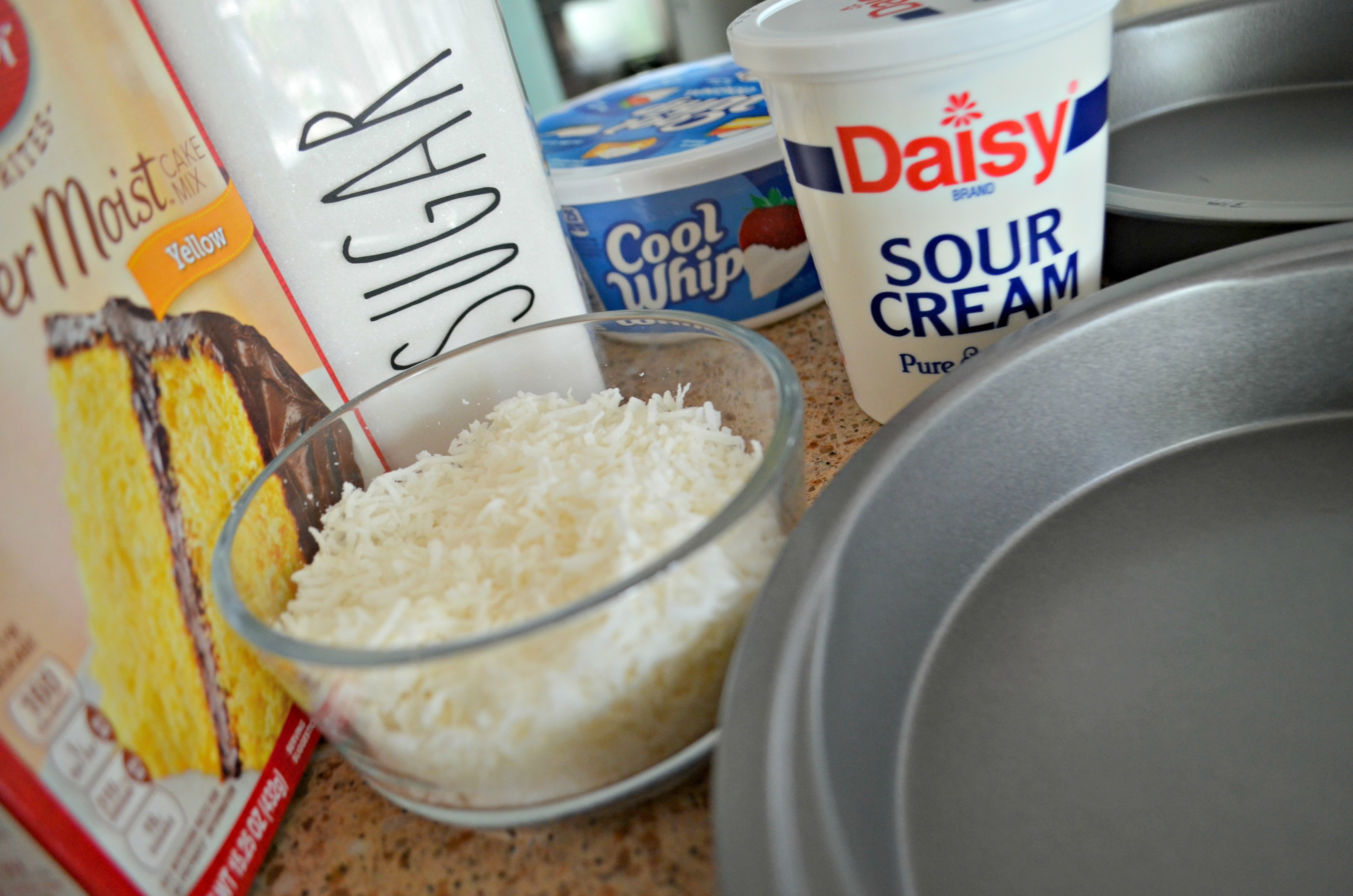 Simple ingredients for this easy coconut cake include a boxed cake mix and sour cream.