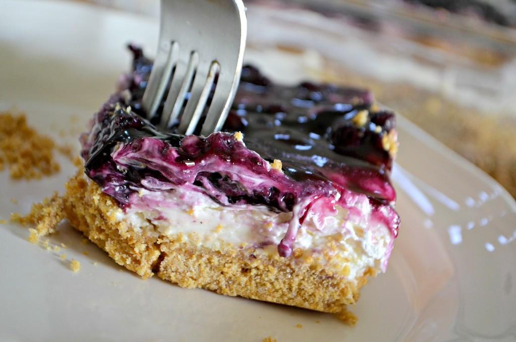fork in blueberry cheesecake dessert
