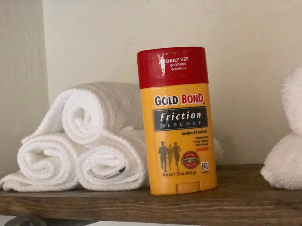 gold bond stick sitting on wood shelf next to white rolled towels