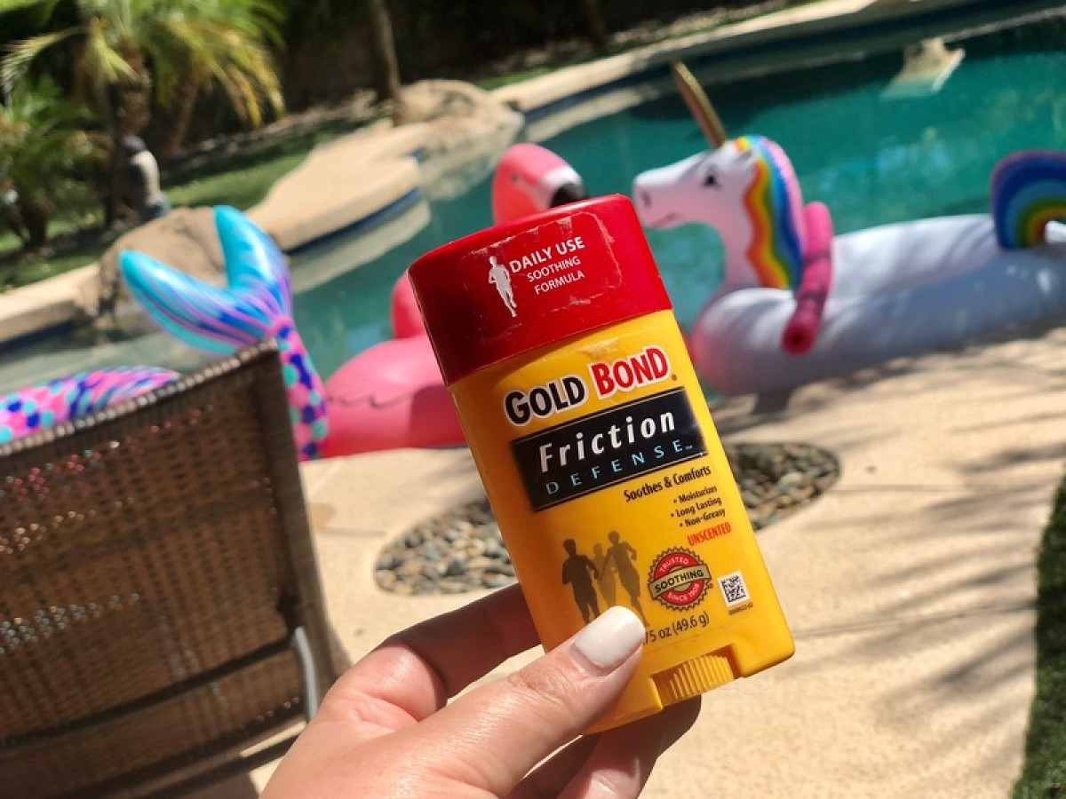 hand holding a gold bond stick in front of in ground pool
