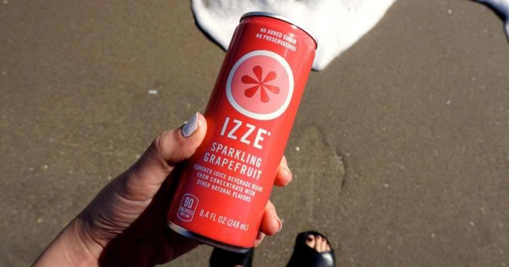 Izze Grapefruit can held by woman on beach