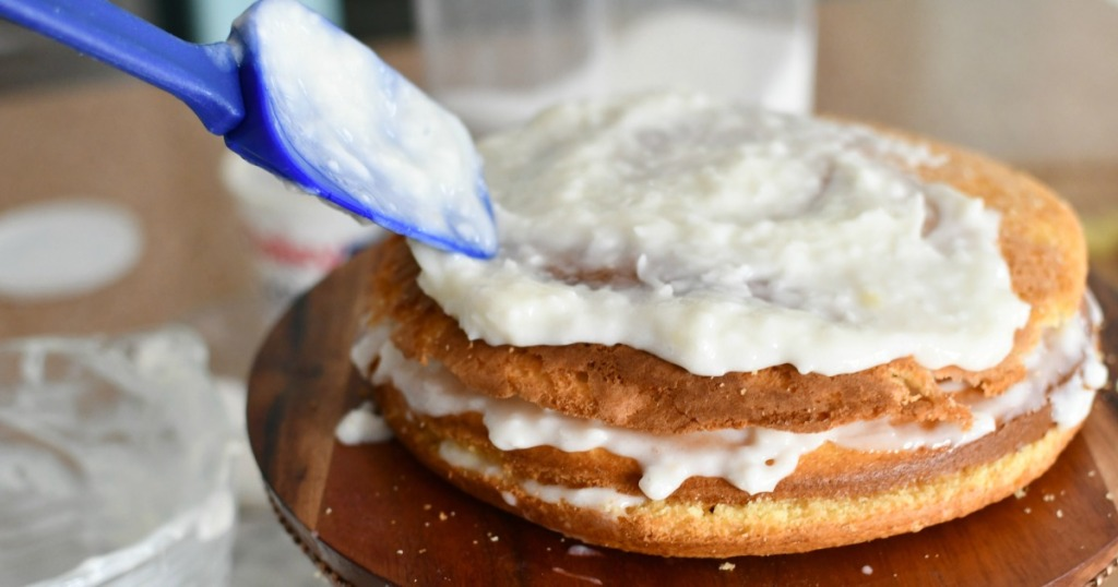 layering sour cream with coconut and sugar onto cake