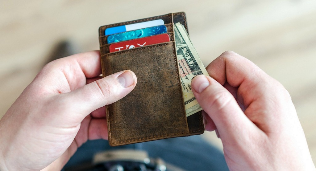 man getting cash out of wallet