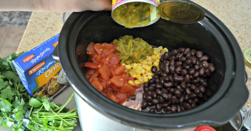 putting ingredients for chicken chili in slow cooker