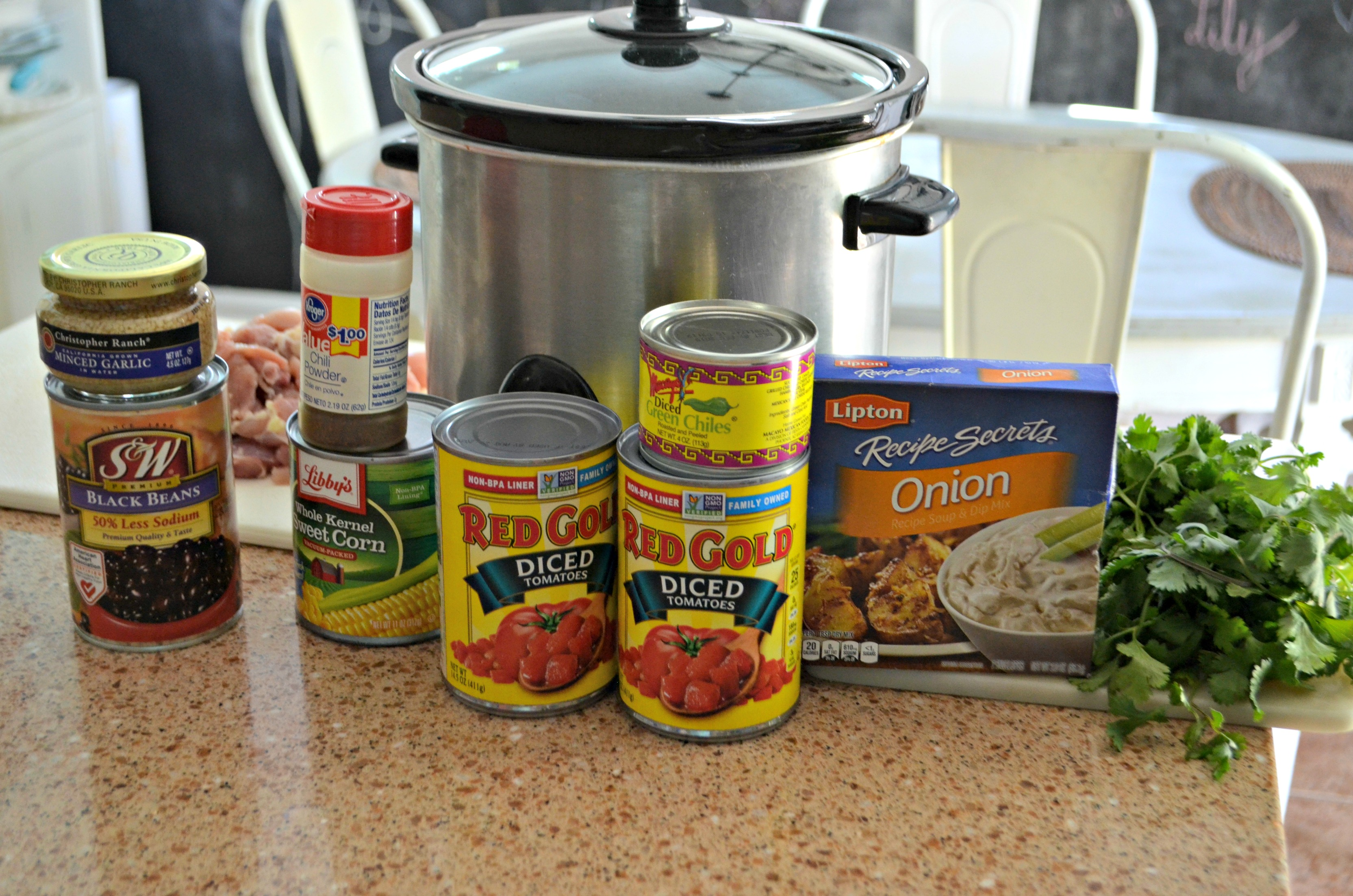 easy slow cooker chicken chili ingredients on the counter with the slow cooker