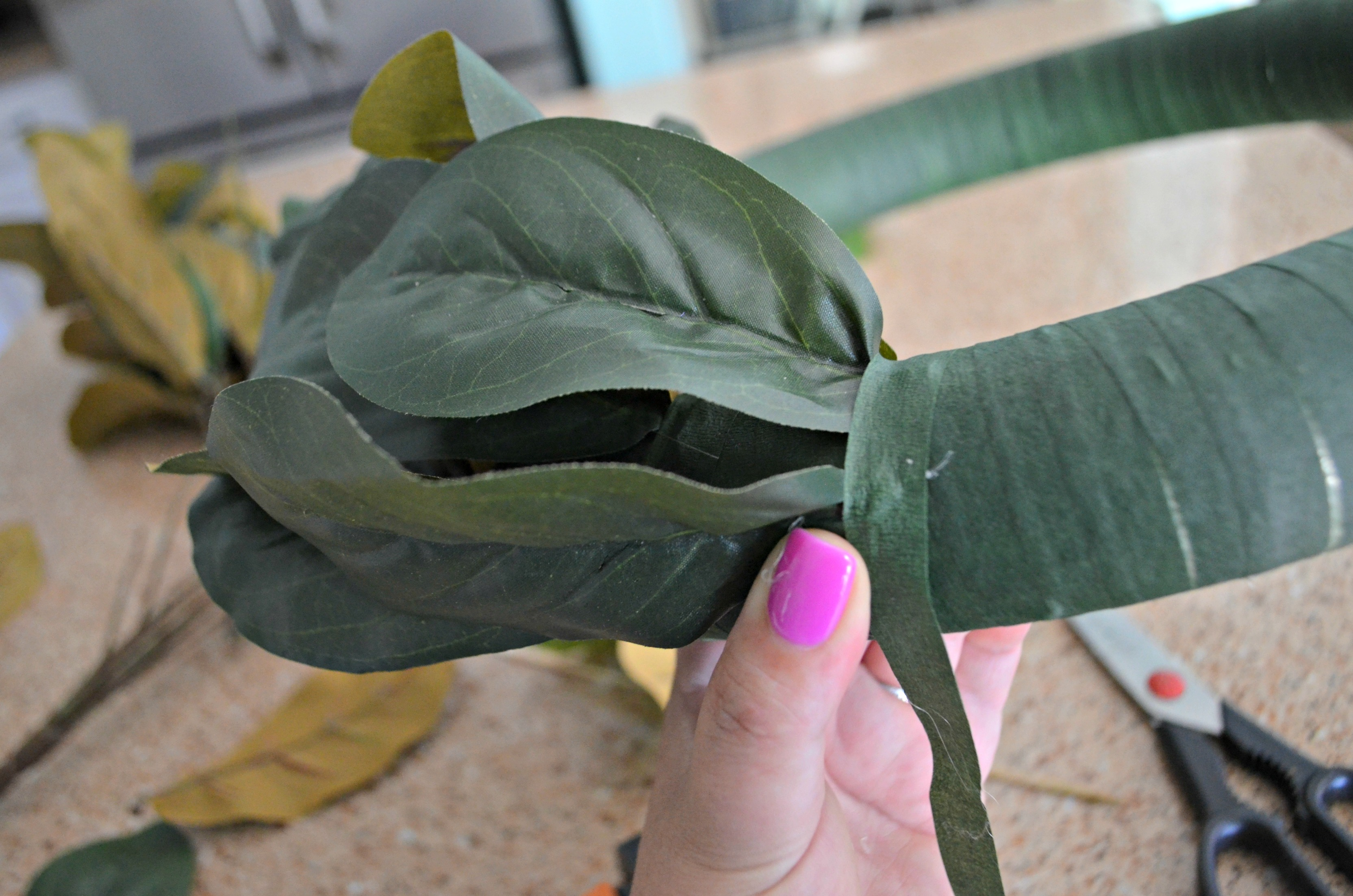 Wrap magnolia stems with tape to secure the ends.