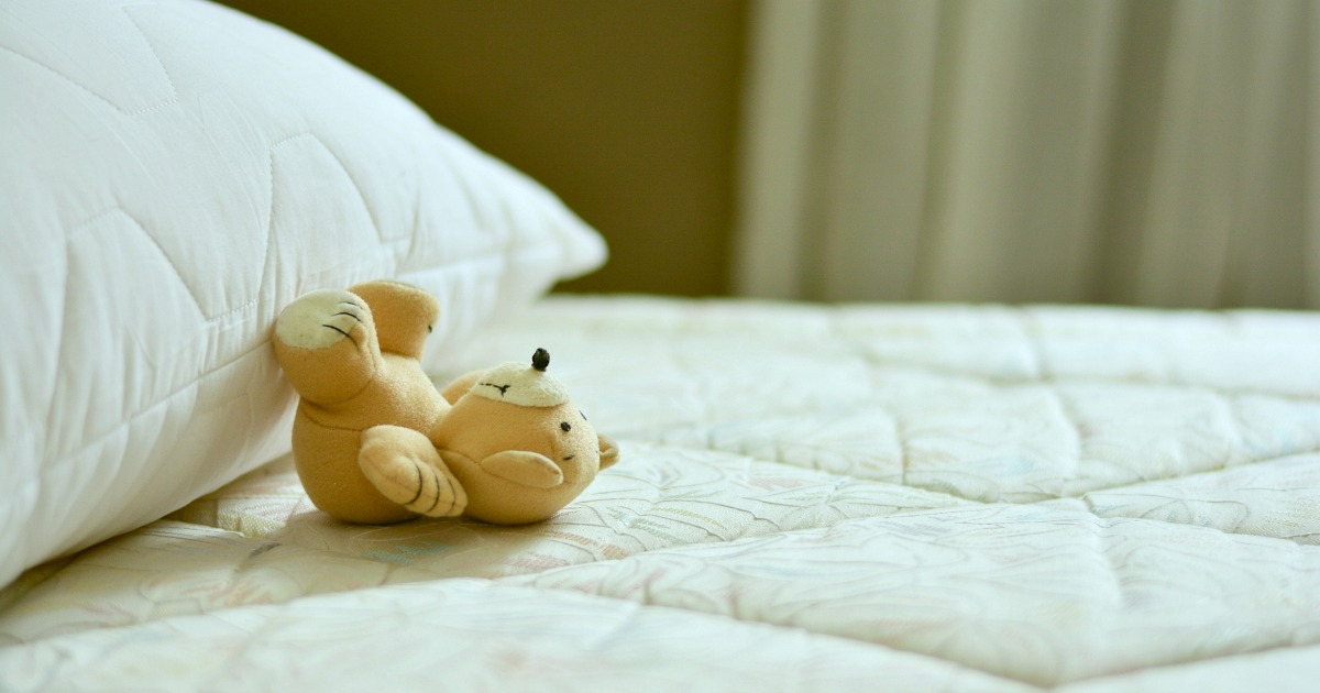 close up of mattress with stuffed teddy bear and pillow