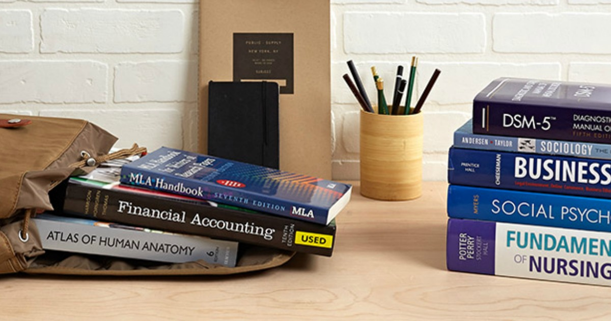 stacks of textbooks and a pencil cup on a desk
