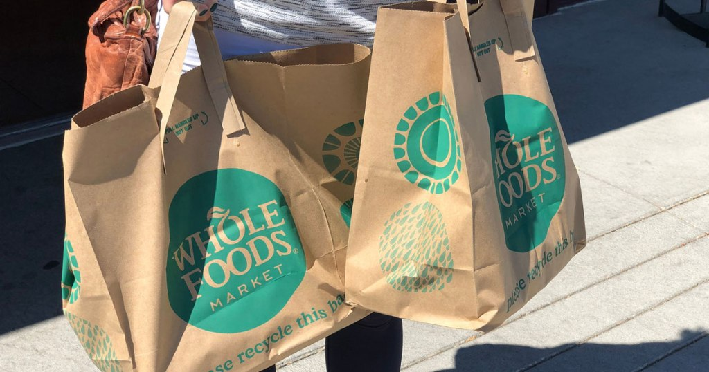 woman carrying Whole Foods shopping bags