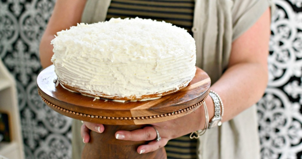 woman holding a coconut sour cream cake