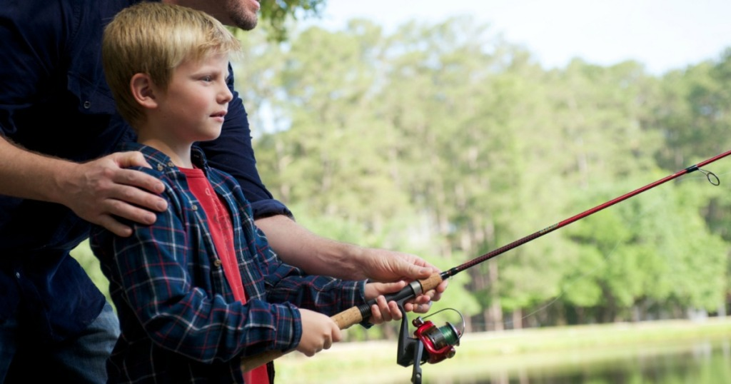 man helping boy with fishing pole