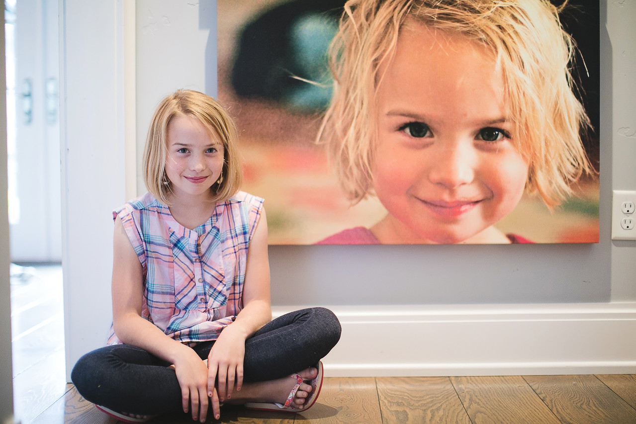 Cute girl sitting in front of custom canvas print