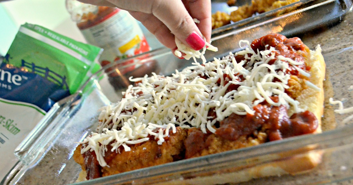 Easy Chicken Parmesan Sliders - sprinkling shredded cheese over the uncooked sliders