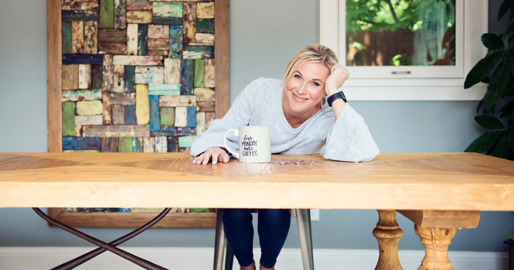 woman with coffee mug sitting at dining table