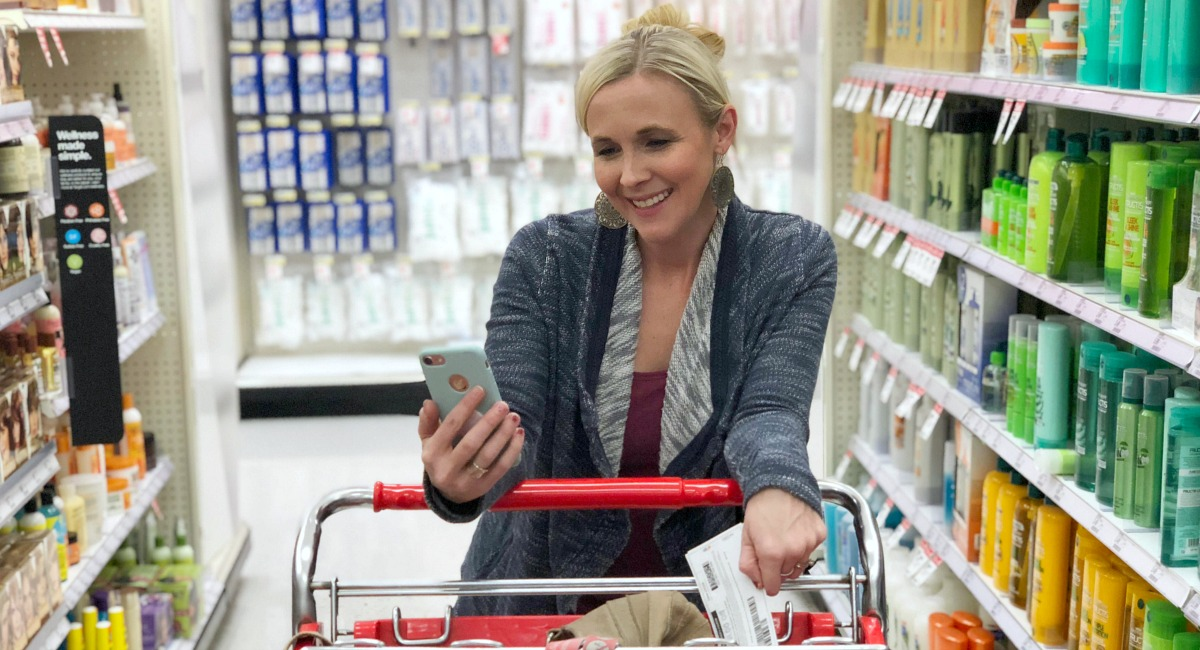 collin smiling at her smart phone while shopping in the store