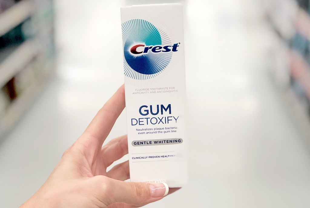Box of Crest-brand gum detoxify toothpaste in hand in store