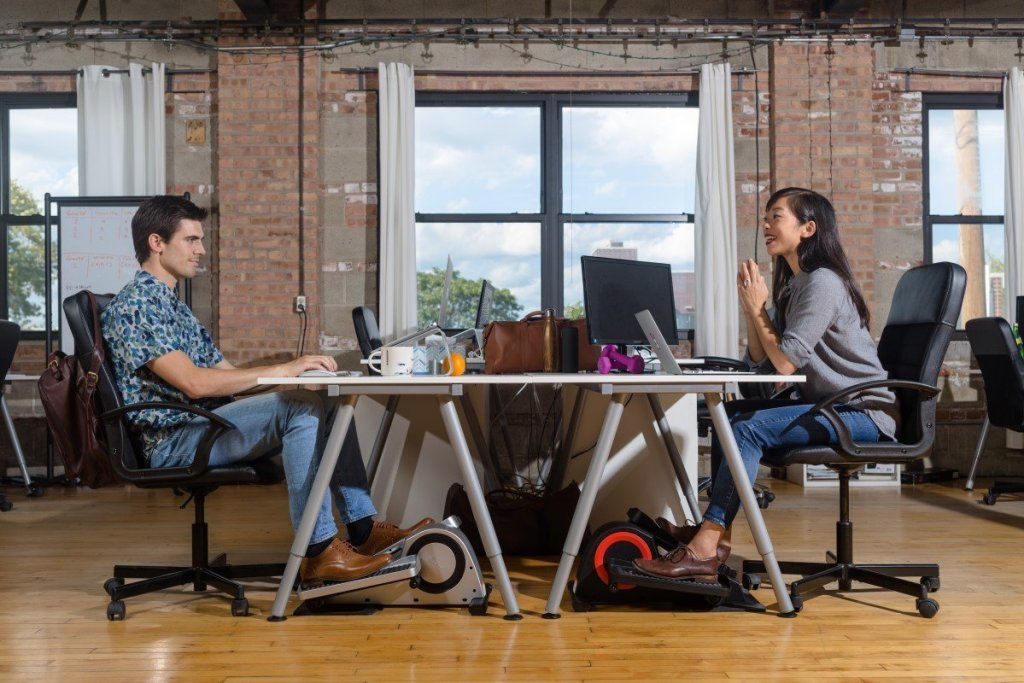 man at woman sitting at opposite sides of desk both using elliptical